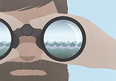 Reflection of sea in binoculars held by a man with a beard