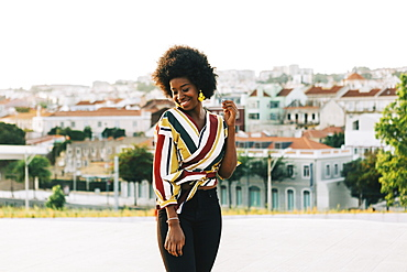 Smiling young woman standing on sunny street, Belem, Lisbon, Portugal