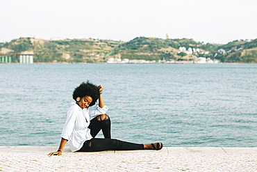 Young woman relaxing at River Tejo waterfront, Belem, Lisbon, Portugal