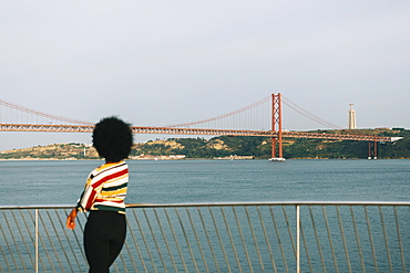 Young woman standing at waterfront, looking at 25 de Abril Bridge and Cristo Rei Statue, Lisbon