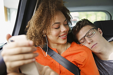 Young couple sleeping and listening to music in car
