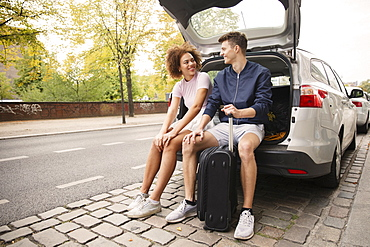 Young couple with suitcase sitting in car hatchback