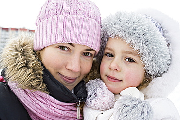 A mother and daughter in warm clothing outdoors in winter