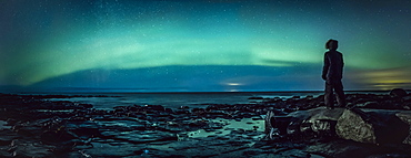 Teenage boy watching Northern Lights from rock, Reykjanesbaer, Iceland