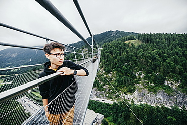 Teenage boy standing on Highline 179 suspension bridge, Tyrol, Austria