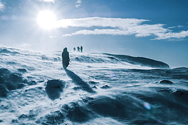 People walking across sunny, windy, snow covered landscape, Reykjadalur, Iceland