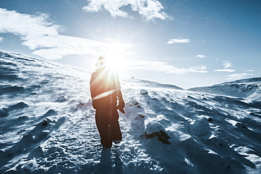 Man walking along sunny snow covered landscape, Reykjadalur, Iceland