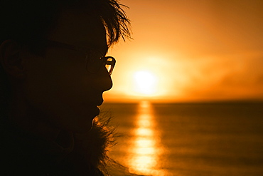 Silhouette profile teenage boy looking at sunset over ocean