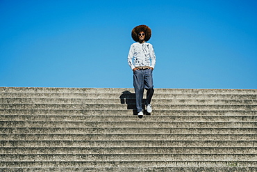 Portrait confident, cool young man with afro on sunny steps