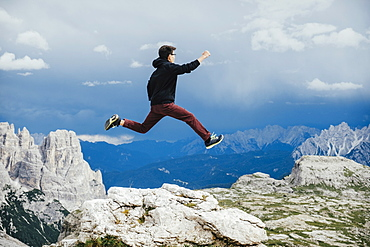 Carefree boy jumping over rocks on mountain, Drei Zinnen Nature Park, South Tyrol, Italy