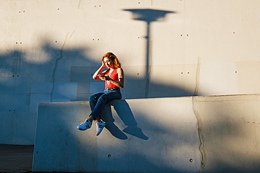Young woman using smart phone on urban wall