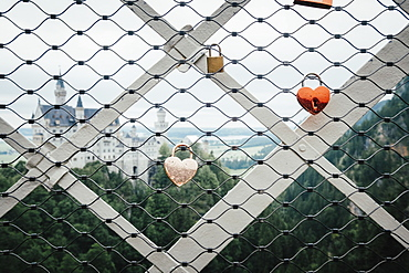 Love lock padlocks on fence overlooking Neuschwanstein Castle, Hohenschwangau, Bayern, Germany