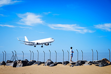 Boy on beach watching airplane flying low in blue sky near Lanzarote Airport, Spain
