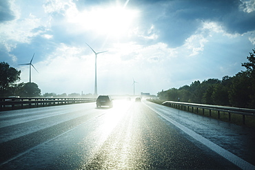 Sun reflecting on wet Autobahn Berliner Ring with wind turbines in distance, Berlin, Germany