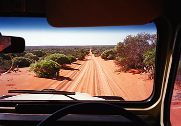 A view of a desert road in Australia through the windshield of an off-road vehicle