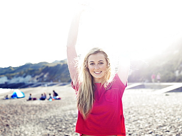 A young woman stretching in the sunlight on a beach
