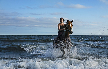 Woman riding horse in ocean surf