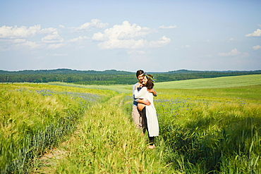 Affectionate pregnant couple hugging in sunny, idyllic rural green field