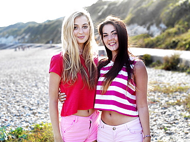 Two smiling young women with their arms around each other standing on a beach