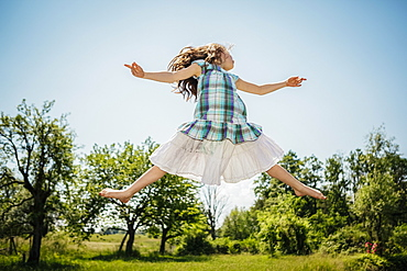 Carefree girl in dress jumping for joy in sunny backyard
