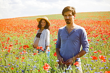 Portrait smiling pregnant couple in sunny, idyllic rural red poppy field