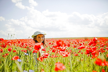Girl in sunny, idyllic rural red poppy field
