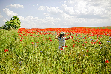 Girl running in sunny, idyllic rural red poppy field
