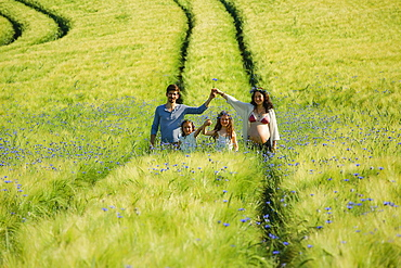 Portrait pregnant family in sunny, idyllic rural green field with wildflowers