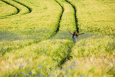 Portrait carefree girl with arms outstretched in sunny, idyllic rural field with wildflowers