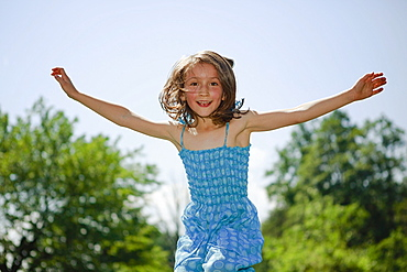 Portrait playful girl with arms outstretched jumping for joy in sunny yard