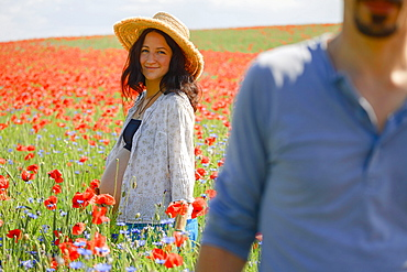 Portrait smiling pregnant woman standing in sunny, rural red poppy field