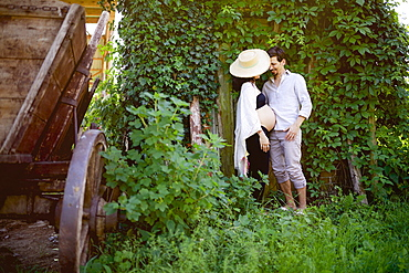 Affectionate pregnant couple standing at ivy covered wall