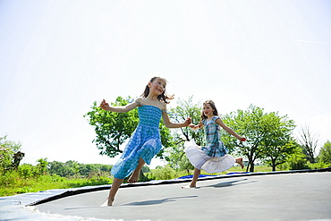 Playful, carefree barefoot girls in dresses playing on trampoline in sunny backyard