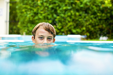 Portrait boy swimming in swimming pool