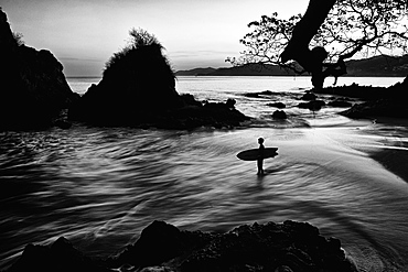 Silhouette boy with surfboard on ocean beach, Sayulita, Nayarit, Mexico