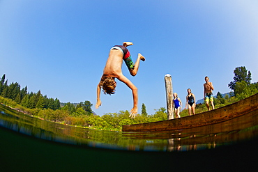 Boy somersaulting off dock into sunny summer lake