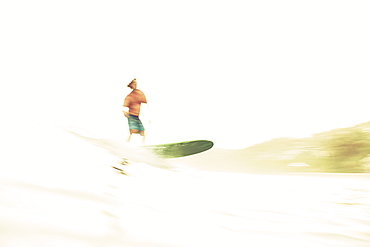 Male surfer riding wave on sunny ocean