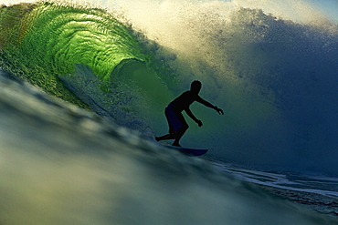 Silhouette male surfer riding backlit ocean wave