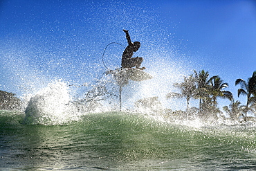 Male surfer catching air above ocean wave, Sayulita, Nayarit, Mexico