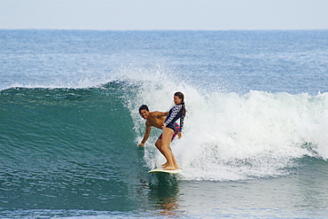 Young couple sharing surfboard, surfing ocean wave