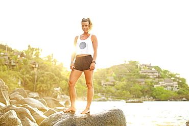 Portrait confident, fit young woman on sunny ocean rocks, Sayulita, Nayarit, Mexico