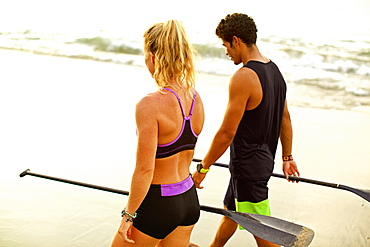 Young, fit couple with oars walking on beach