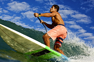 Fit young man paddleboarding ocean wave