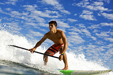 Young man on paddleboard riding ocean wave