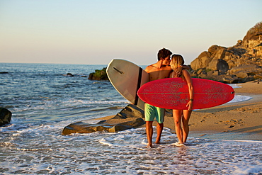 Young, affectionate couple with surfboards walking on sunny ocean beach, Sayulita, Nayarit, Mexico