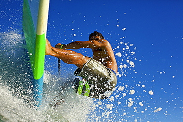 Young man riding paddleboard on ocean wave