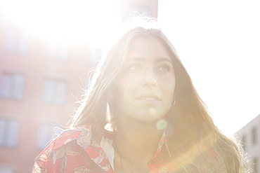 Young woman standing under sunshine, close-up