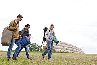 Men and woman carrying camping accessories and walking through filed