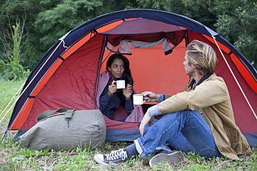 Young couple in dome tent having drink