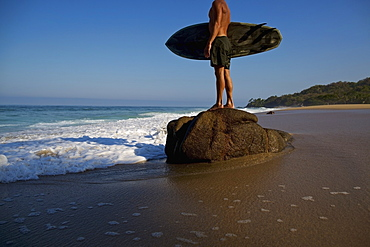 Male surfer with surfboard standing on large stone on beach, Sayulita, Nayarit, Mexico